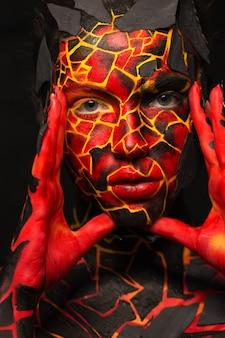 黒い壁に塗られた顔を持つ少女。悪魔の形のボディーアート