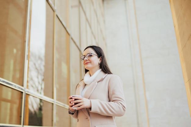 Девушка с бумажным стаканчиком кофе