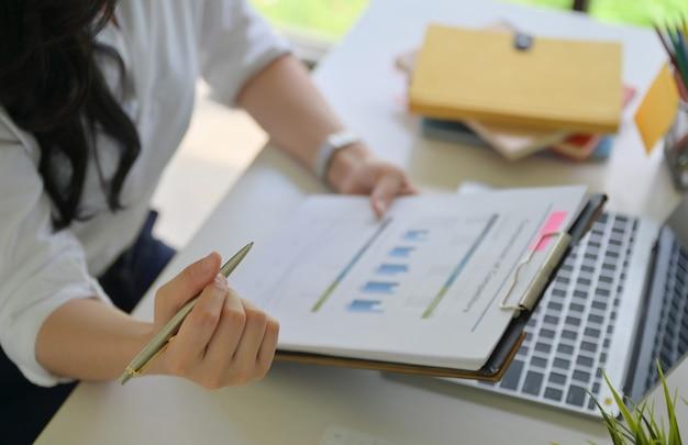Девушка с ручкой и графиками данных проверяет данные в офисе, имеющем ноутбук на столе.
