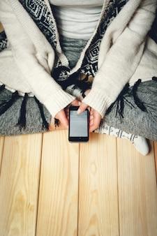 나무 바닥에 앉아 그녀의 손에있는 전화 소녀. 평면도