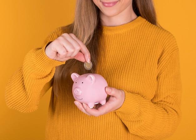 貯金箱を持つ少女は、金融危機の概念を保存するために、コインを挿入します