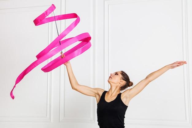 여자를 위한 리듬 체조 스포츠의 개념 분홍색 체조 리본을 가진 소녀