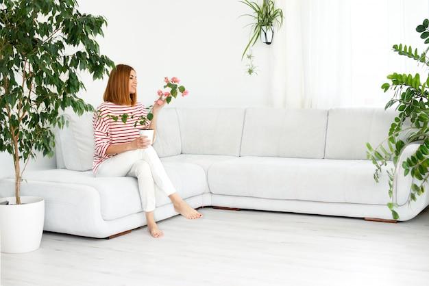 Девушка с растением в горшке. улыбается настоящая женщина дома. белый салон. копировать пространство