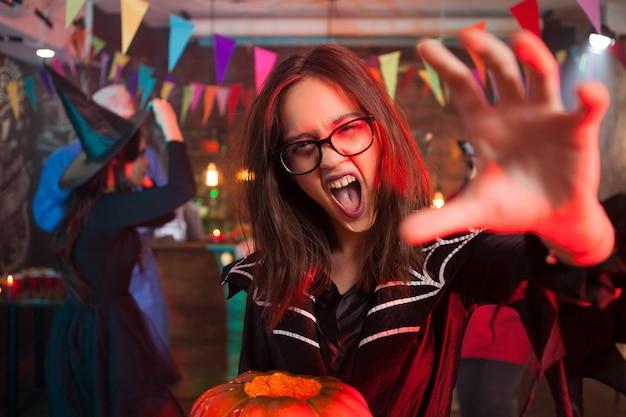 ハロウィーンの叫び声とカメラに手を差し伸べるためのカボチャを持つ少女。ハロウィーンパーティーで美しい少女の肖像画をクローズアップ。