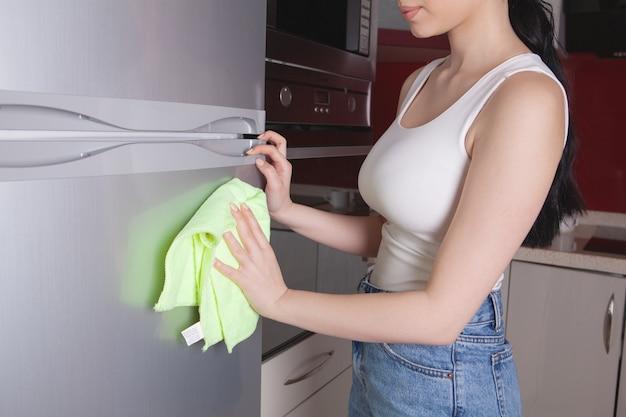冷蔵庫を掃除するぼろきれの女の子