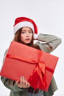 Девушка с красным большим подарком в руках санта шляпа привлекательный взгляд студия новый год