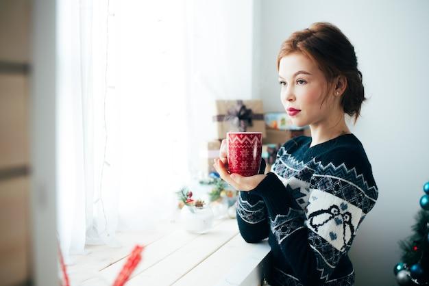 크리스마스 트리 배경에서 창문 근처에 빨간 머그잔을 들고 있는 소녀