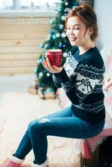 크리스마스 트리 배경의 창문 근처에 손에 빨간 머그잔을 들고 있는 소녀