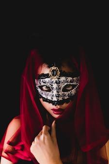 Девушка с красным шарфом на голове и венецианские маски