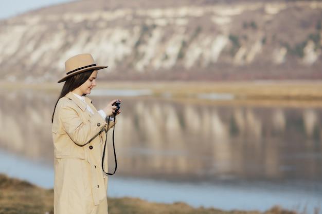 Девушка с ретро фотоаппаратом в руке смотрит на фотографии