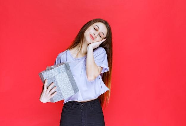 은색 선물 상자를 든 소녀는 피곤하고 졸려 보입니다.