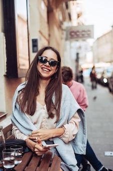 ストリートカフェに座っているスマートフォンを持つ少女。