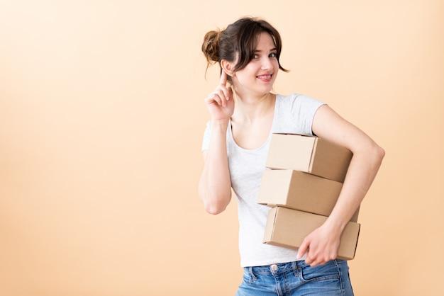 Девушка с улыбкой подслушивает с коробками в руках. курьер всегда готов выслушать. девушка на бежевом пространстве.