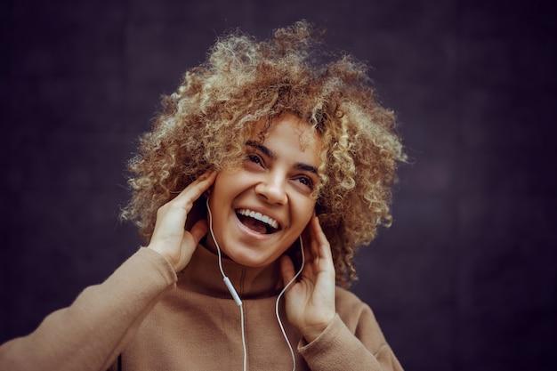 그녀의 귀에 손을 잡고 음악을 즐기는 그녀의 얼굴에 미소를 가진 소녀.