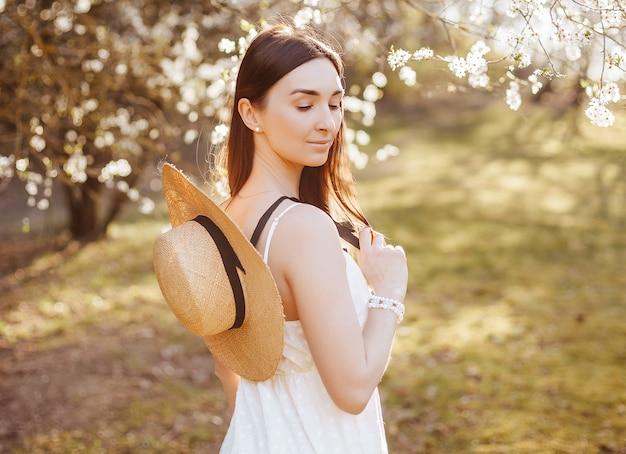 공원에서 봄에 밀 짚 모자 소녀. 긴 머리를 가진 갈색 머리는 여름 자연의 배경에 모자를 보유하고 있습니다. 젊음과 아름다움.