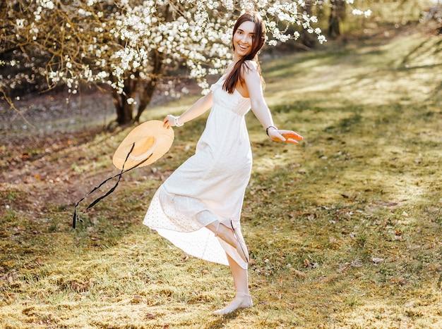 公園で春に麦わら帽子をかぶった少女。長い髪のブルネットは、夏の自然を背景に帽子をかぶっています。若さと美しさ。