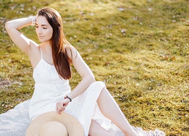 公園で春に麦わら帽子をかぶった少女。夏の自然の表面の格子縞の上に座っている長い髪のブルネット。若さと美しさ。