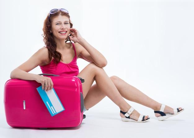 白い背景で旅行に行くスーツケースを持つ女の子