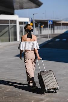 スーツケースを持った女の子が駅でバスを探して旅をする