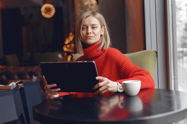 タブレットを持つ少女。カフェの女性。テーブルに座っている女性。