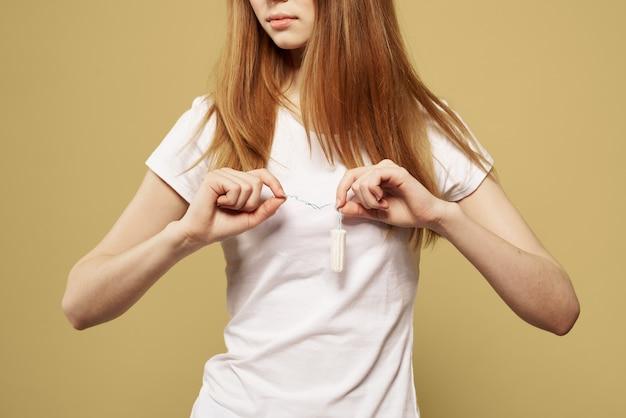 月経の危機的な日々の姿の大きさを手にタンポンを持った少女