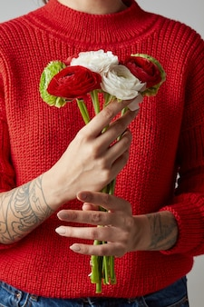 빨간 니트 스웨터를 입은 손에 문신을 한 소녀는 꽃다발을 들고 있습니다. 해피 발렌타인 데이