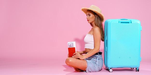 Девушка с билетами и деньгами отправится в путешествие, сидя возле чемодана в шортах, белом топе и соломе ...