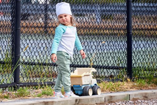 遊び場でおもちゃのトラックを持つ少女