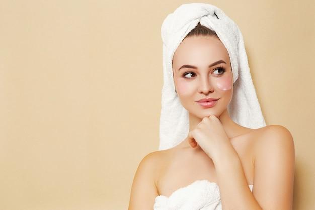 Девушка с белым полотенцем на голове на бежевом фоне