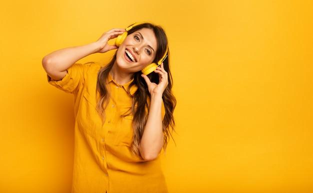 Девушка с желтой гарнитурой слушает музыку и танцует