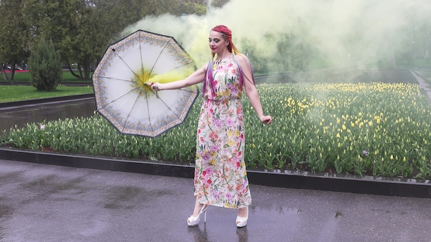 아프리카 머리띠와 봄 드레스에 화장을 한 소녀가 춤을 추고 있습니다