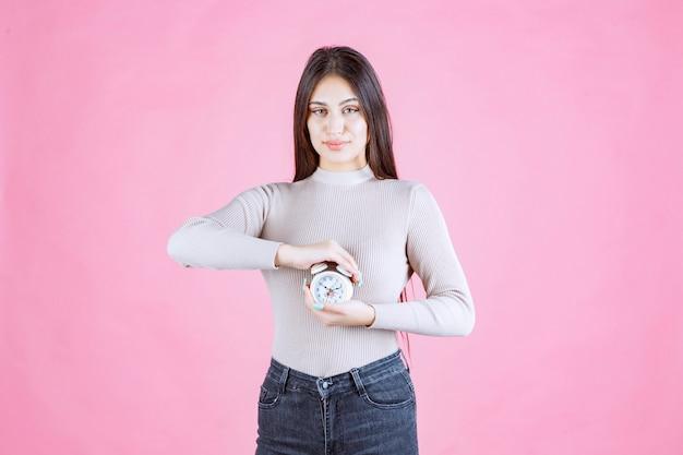 Девушка с будильником, держа его в руках