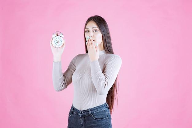 알람 시계를 가진 소녀는 침묵 기호를 만든다