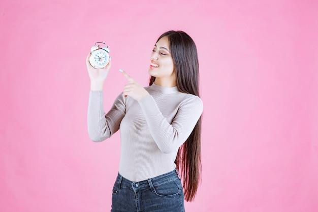 それを指している目覚まし時計を持つ少女