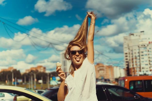 アイスクリームの女の子彼女の舌を突き出して、彼女の髪を引っ張っ