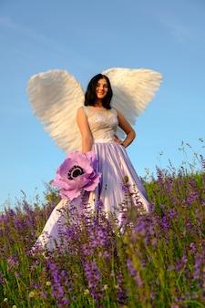 Девушка с крыльями ангела стоит на склоне холма и держит большой фиолетовый цветок