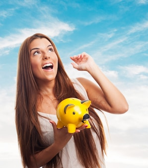 Girl with arm up holding moneybox