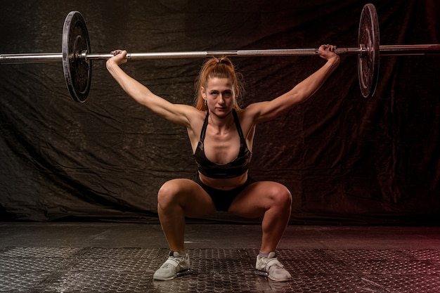 A girl with an athletic physique is engaged in crossfit