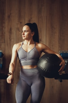 Girl with athletic physique posing with fitball on the background of the wooden wall of the gym for crossfit