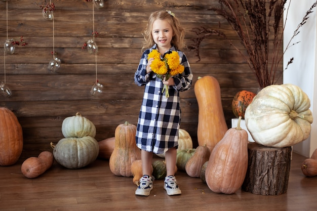 Girl with autumn yellow flowers bouquet at home