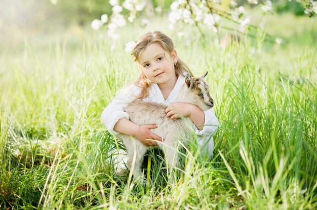 Girl with baby goat. friendship of child and animals. happy childhood.
