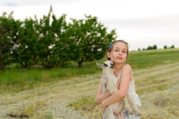 야외 농장에서 아기 염소와 소녀입니다. 사랑과 보살핌. 마을 동물. 행복한 아이가 염소를 안아