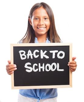 学校の黒板に背を持つ少女