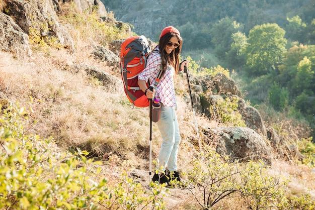 Девушка с рюкзаком и лыжной палкой возле каньона в полный рост