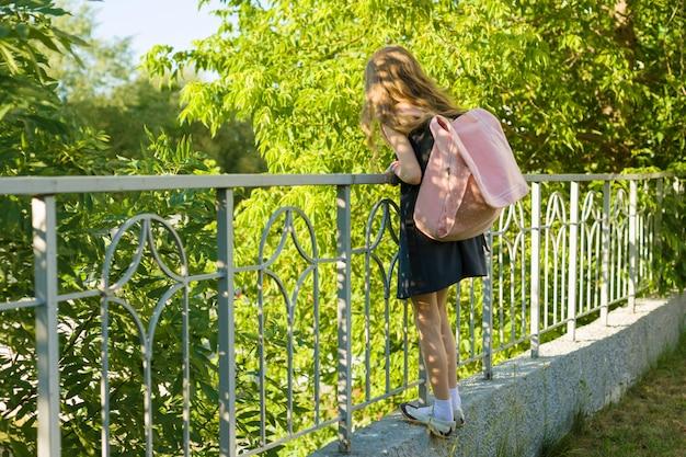 学校の制服を着たバックパックを持つ少女