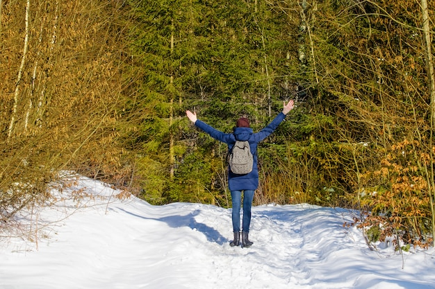 Girl with a backpack is standing with arms raised in a snowy forest