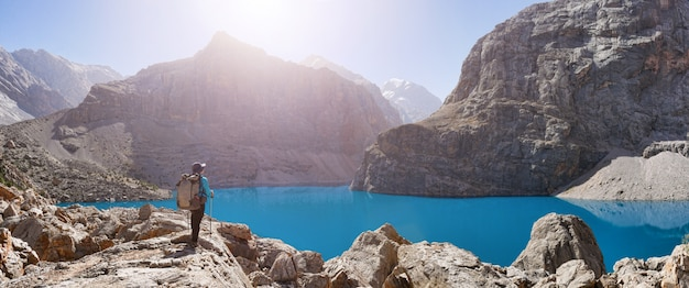 Girl with backpack near lake big alo on rocky mountain background. fann mountains, tajikistan, central asia