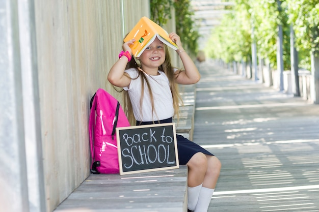 Girl with a backpack in the park.first day of school