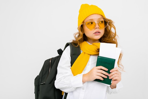 Girl with a backpack, scarf, hat and passport with tickets on a white wall