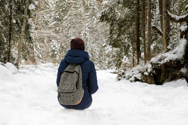 雪に覆われた針葉樹林に座っているバックパックを持つ少女。